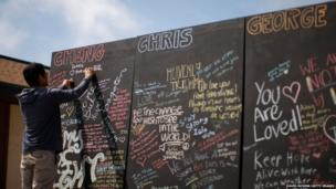 A student writes chalk messages on a memorial wall for slain students on the Day of Mourning and Reflection for the victims of a killing spree at University of California, Santa Barbara