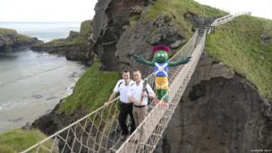 Two men pose with the Queen's Baton on a narrow rope bridge accompanied by a person dressed as a cartoon thistle.
