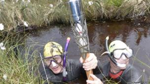 Two men wearing wetsuits and snorkelling equipment hold the Queen's Baton clear of the peat bog they are almost submerged in.