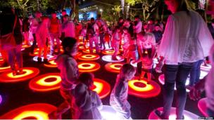 Kids are having fun jumping on lit up circles on the ground.