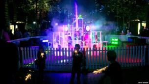 These children are helping make the festival more luminous as they play with sparklers in front of one of the displays.