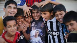 Iraqi boys play football in Sadr City in Baghdad on 29 May 2014.