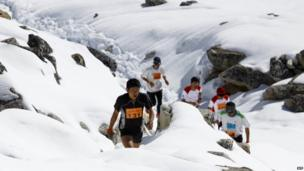 Men make their way through the snowy and rocky terrain of the course.