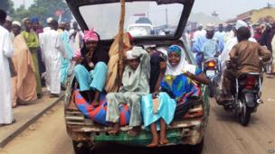 Young girls take a ride in an open car boot on a street in the Nigerian city of Maiduguri on 24 May 2014