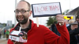 """Tram enthusiast with sign """"I love trams"""""""