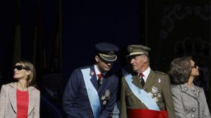 Spain's Crown Prince Felipe (2nd L) and King Juan Carlos talk as Princess Letizia (L) and Queen Sofia (R) watch a military parade during Spain's National Day in Madrid