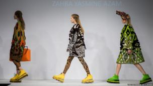 Models walk the runway wearing designs by Zahra Yasmine Azam during Graduate Fashion Week at The Old Truman Brewery in London, England