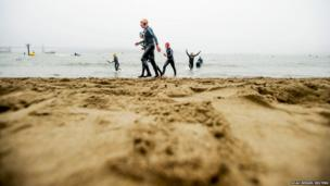 Swimmers emerge from the water in San Francisco Bay during the 34th annual Escape from Alcatraz Triathlon
