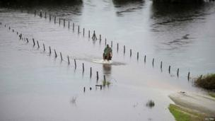 A resident rides his horse along a flooded road near Puerto Varas city, south of Santiago