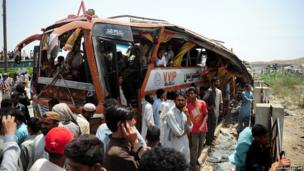 Local residents gather around the wreckage of a bus after a Pakistan air force fighter plane crashed at a bus terminal on the outskirts of Karachi