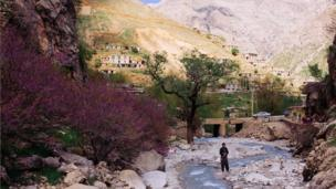 A man prays in a river in the Hawraman valley