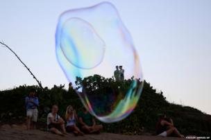 Tourists watch giant soap bubbles created by German street artist Florian Timm on Ipanema beach in Rio de Janeiro, Brazil