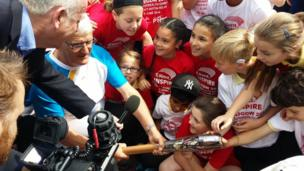 Children with baton-bearer John Simmonds and a TV crew in Dartford