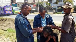 Three men doing a woman's hair in Nairobi, Kenya - Saturday 31 May 2014