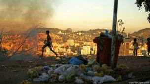 A trash fire burns due to the lack of government assistance of trash disposal in the Mangueira favela ,which overlooks the Maracana Stadium in Rio de Janeiro (5 June 2014)