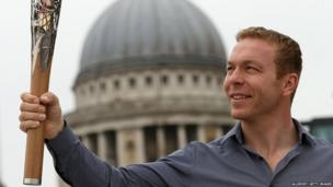 Ambassador and Olympic gold medallist Sir Chris Hoy holds the Queens Baton in front of St Pauls Cathedral