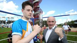 Baton bearer Jonathan Webb and Barry McGuigan hold the Queens Baton in front the Orbit tower