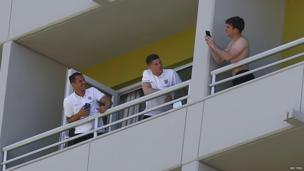 Leighton Baines, Phil Jagielka and Ross Barkley take pictures on their balconies.