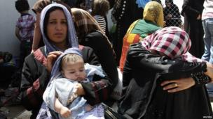 Families fleeing the violence in the Iraqi city of Mosul wait at a checkpoint on the outskirts of Erbil, on 10 June 2014.