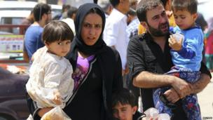 A family fleeing the violence in the Iraqi city of Mosul waits at a checkpoint near Irbil, in Iraq's Kurdistan region, 10 June 2014