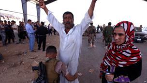 An Iraqi Kurdish security guard frisks a man as he waits at a checkpoint