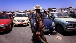Iraqis fleeing violence in the Nineveh province wait in their vehicles at checkpoint west of Erbil, on 10 June 2014.