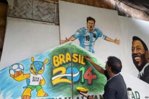 A city painter gives finishing touches to posters of Argentine player Lionel Messi and Brazilian soccer legend Pele at a local football club.