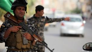 Iraqi policemen man a checkpoint in the capital Baghdad on 10 June 2014, after a state of emergency was declared by the government