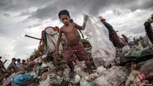 Scavenger boy grabs plastic between tons of rubbish in in Siem Reap, Cambodia.
