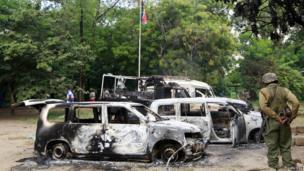 Wreckages of burnt cars are seen outside Mpeketoni police station after unidentified gunmen attacked coastal Kenyan town of Mpeketoni