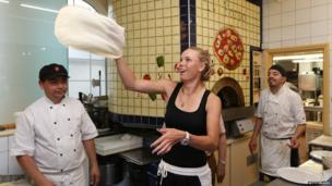 Caroline Wozniacki of Denmark makes a pizza at Pomodore e Mozzarella ristorante in Eastbourne on day two of the Aegon International at Devonshire Park on June 15, 2014 in Eastbourne, England