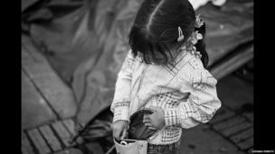 A girl looks into her bag on Plaza Bolivar in Bogota.
