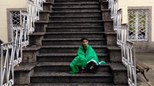 Boy sat on stairs with flag around him