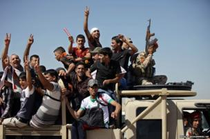 Iraqi men flash victory signs as they leave the main recruiting centre to join the Iraqi army in Baghdad, Iraq