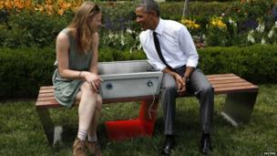 "US President Barack Obama speaks to eco-friendly urban furniture designer Sandra Richter at the first White House ""Maker Faire"". 18 June 2013"