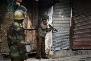 A policeman aims his pellet gun at the group of Kashmiri protesters during a strike in Srinagar, the summer capital of Indian Kashmir, January 31 2014.
