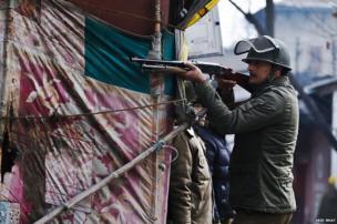 A policeman aims his pellet gun at Kashmiri protesters during a strike in Srinagar, the summer capital of Indian Kashmir, January 31 2014.