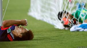 Japan's Yoshito Okubo (left) lies on the ground after failing to score a goal as Greece's goalkeeper Orestis Karnezis looks on