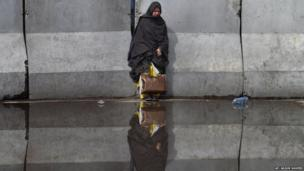 A stranded passenger waits for the opening of the entry gate of Benazir International airport on 23 June 2014