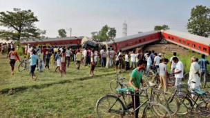 People gather around a passenger train that derailed near Chhapra town in Bihar, India