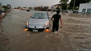A man wades out to help a driver in a partially-submerged car in Fort Worth, Texas