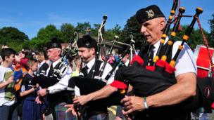 The Mayfield Pipe Band escort the baton into Newbattle High School