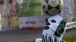 A Nigerian man heads the ball to entertain fans at a viewing centre in Lagos on 25 June 2014