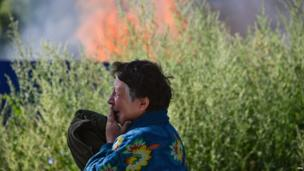An Ukrainian woman cries in front of her house which was destroyed by shelling in Slaviansk, Donetsk region, Ukraine