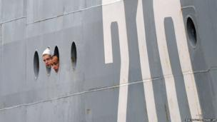 Russian sailors look through the porthole as they arrive aboard the Smolniy in Saint-Nazaire, France