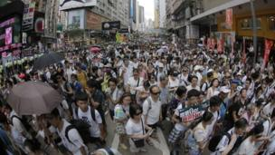 People fill in a street during a march at an annual democracy protest in downtown Hong Kong (1 July 2014)