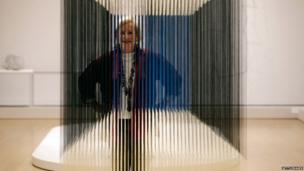 """Patricia Phelps de Cisneros poses with the artwork """"Nylon Cube"""" by Venezuelan artist Jesus Soto, part of the exhibition Radical Geometry: Modern Art of South America from the Patricia Phelps de Cisneros Collection at the Royal Academy of Arts (1 July 2014)"""