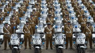 Sri Lankan policemen stand next to their new motorcycles at a ceremony in Colombo (1 July 2014)
