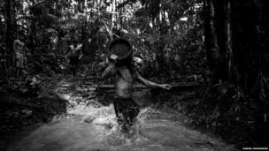 A player participates in a log race in the Amazon jungle