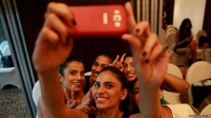 An Indian model takes a photograph of herself with other models